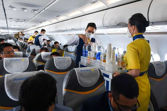 Flight attendants serve water and soft drink on a Vietravel Airlines flight in this supplied photo.