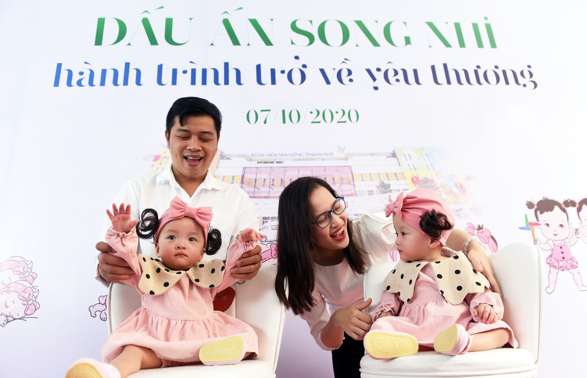 Truc Nhi and Dieu Nhi and their parents are pictured in Ho Chi Minh City on October 7, 2020. The conjoined twins underwent a separation surgery in July 2020. Photo: Duyen Phan / Tuoi Tre