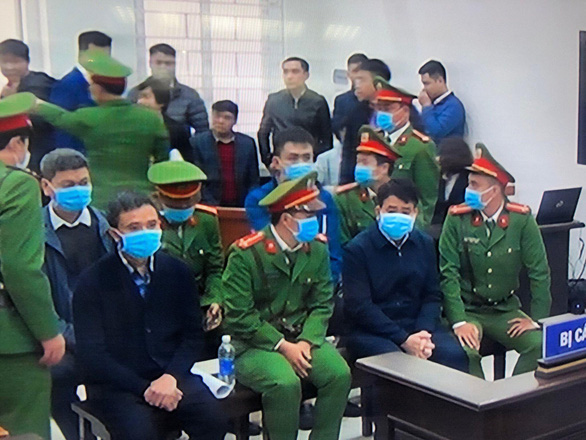 Nguyen Duc Chung (first row, second right) and his accomplices are seen during their trial at the Hanoi People's Court on December 11, 2020. Photo: Nam Tran / Tuoi Tre