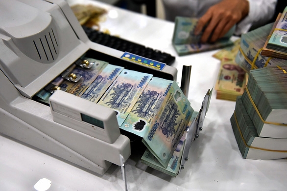 Banknotes are seen in a counter machine at a bank in Ho Chi Minh City. Photo: Ngoc Phuong / Tuoi Tre