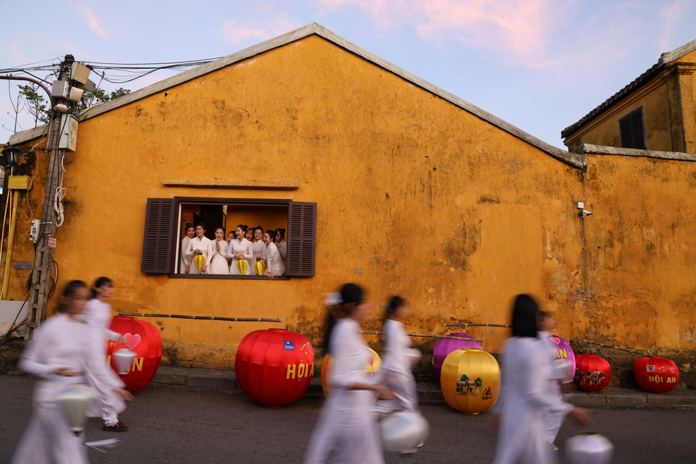 A group of women watch students patrolling with lanterns in their hands from a window in Hoi An Ancient Town, Quang Nam Province, Vietnam, December 28, 2020. Photo: Le Trong Khang / Tuoi Tre