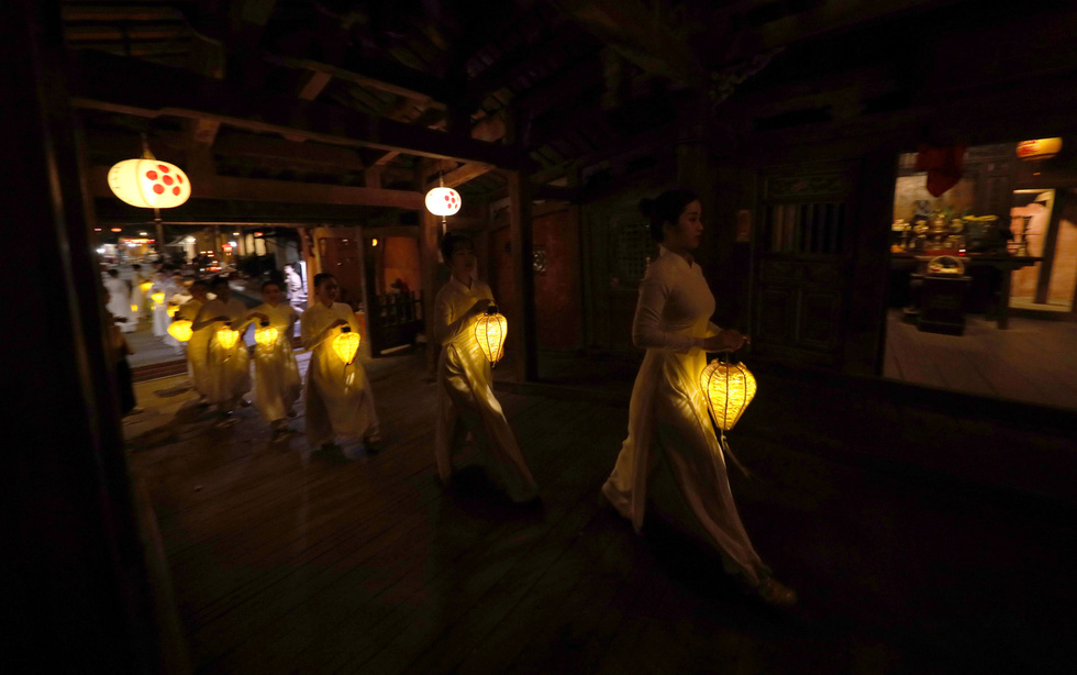 Artists donning Vietnam's traditional 'ao dai' walk in a long line with lanterns in their hands in Hoi An Ancient Town, Quang Nam Province, Vietnam, December 28, 2020. Photo: Le Trong Khang / Tuoi Tre