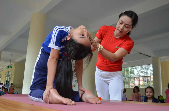 Tran Thanh Nhanh instructs a young student at Mac Dinh Chi Elementary School, located in Can Tho City, southern Vietnam, how to perform the Camel Pose. Photo: Minh Tam/ Tuoi Tre