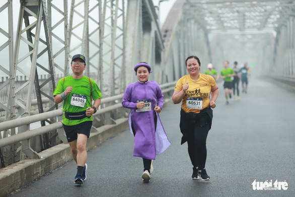 A female runner is seen wearing purple ao dai while competing at the VnExpress Marathon Hue 2020. Photo: Nguyen Dong / Tuoi Tre
