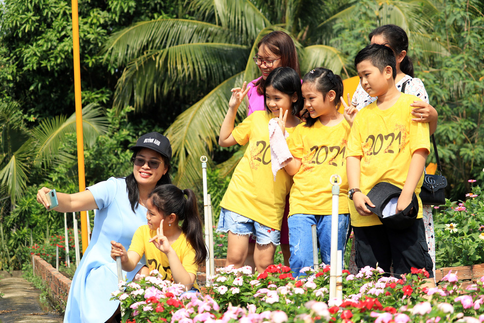Families take a selfie at a botanical garden in Ho Chi Minh City's Nhi Binh Ward.