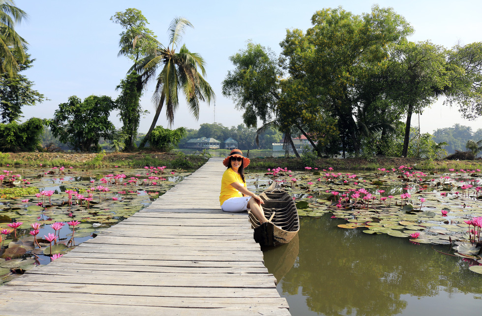 A visitor poses for the camera at a botanical garden in Ho Chi Minh City's Nhi Binh Ward.