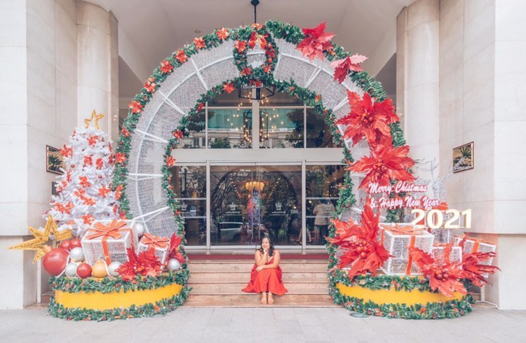 American travel blogger Samantha poses for a picture in front of a building in downtown Ho Chi Minh City  decorated to celebrate the occasion of Christmas and New Year of 2021. Photo: Supplied