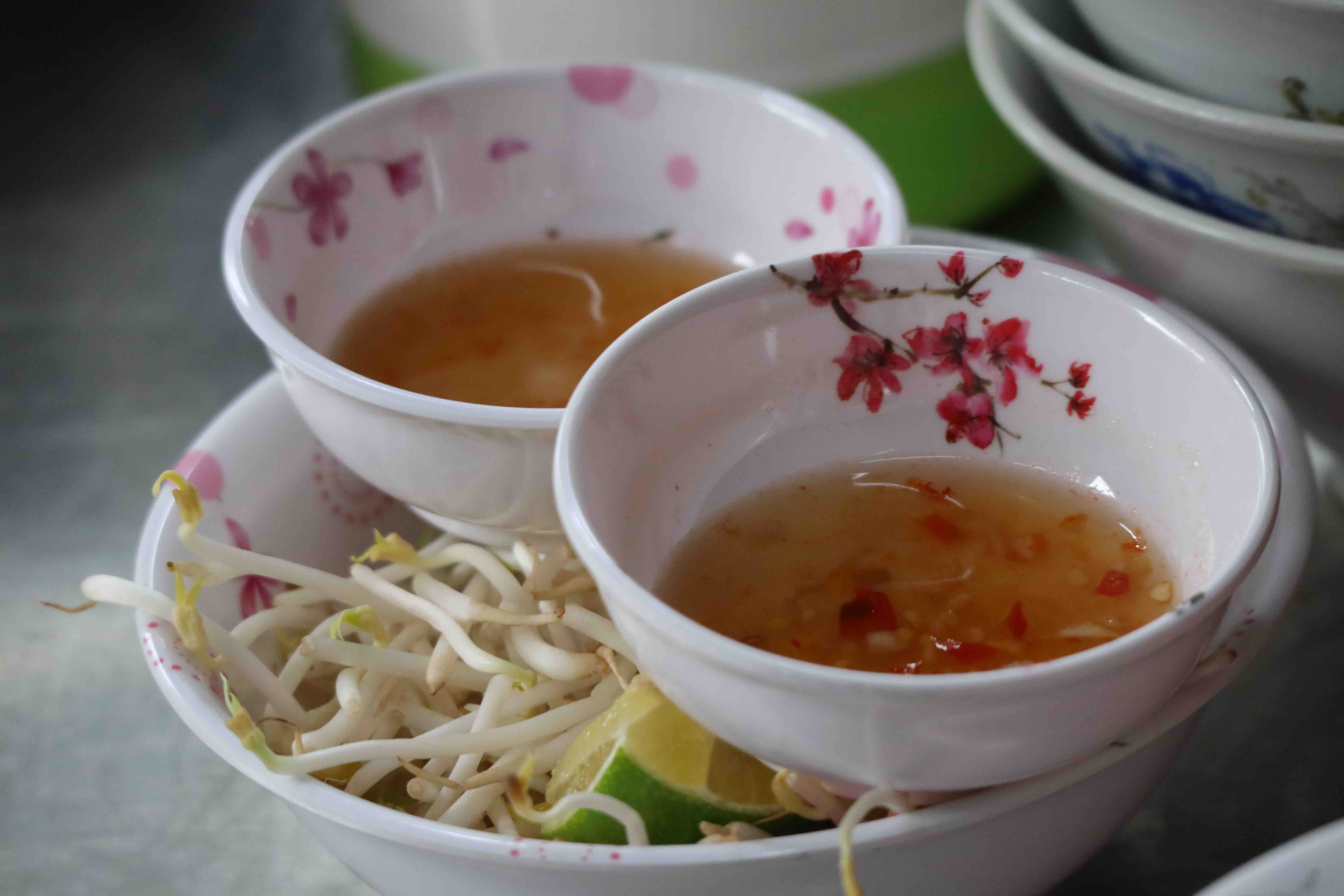 A portion of porridge at Chao Long Ba Ut comes with homemade dipping sauces and a bowl of vegetables. Photo: Nam Vuong / Tuoi Tre