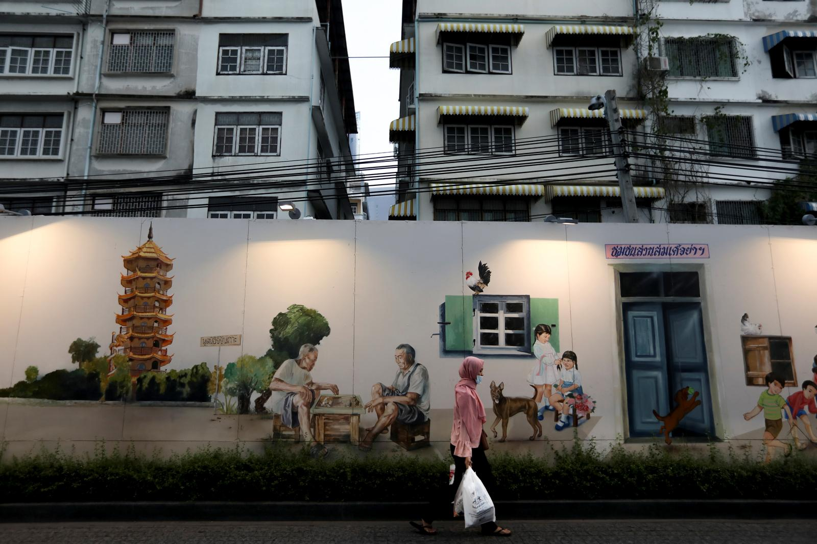A woman walks past a mural depicting scenes of traditional street life outside Iconsiam shopping mall in Bangkok, Thailand, January 31, 2019. Photo: Reuters