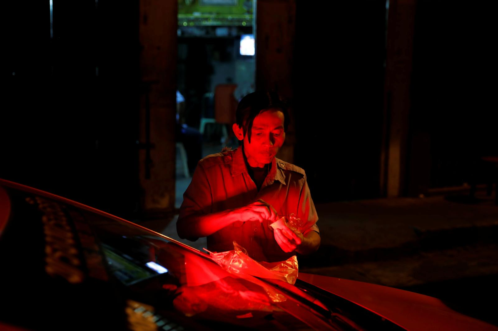 A taxi driver eats dinner next to his car in the historic neighbourhood of Talad Noi in Bangkok, Thailand, December 13, 2018. Photo: Reuters