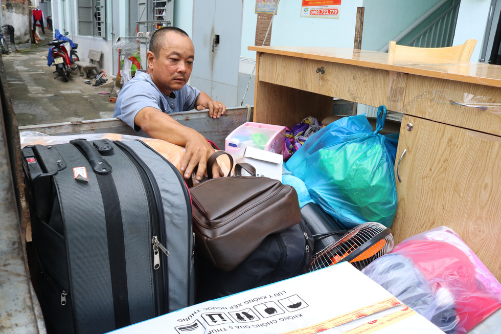 Le Van Duc checks a student's personal belongings and furniture before transporting them to a new home. Photo: Hoang An / Tuoi Tre