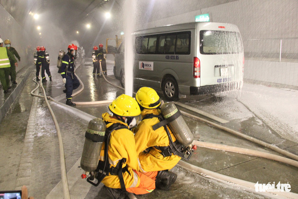 Firefighters spray water to a burning vehicle during a fire drill inside the Hai Van Tunnel 2 in central Vietnam, December 30, 2020. Photo: Truong Trung / Tuoi Tre
