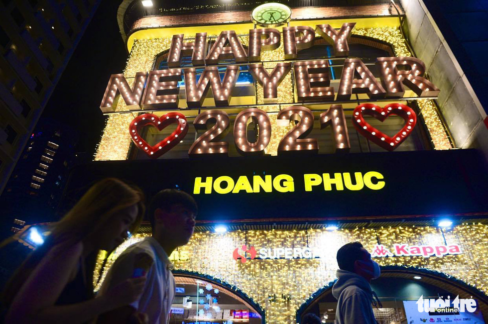 """A fashion store on Nguyen Hue Street is seen with """"Happy New Year 2021"""" signage, December 31, 2020. Photo: Quang Dinh / Tuoi Tre"""