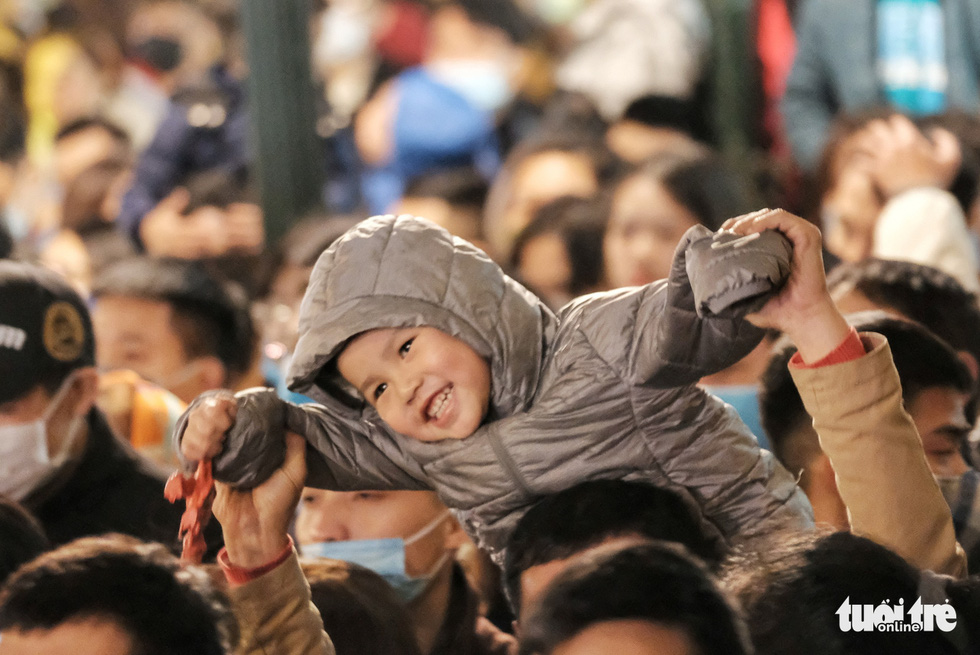 A child enjoys the countdown party show near Hanoi's Hoan Kiem Lake, December 31, 2020. Photo: Mai Thuong / Tuoi Tre
