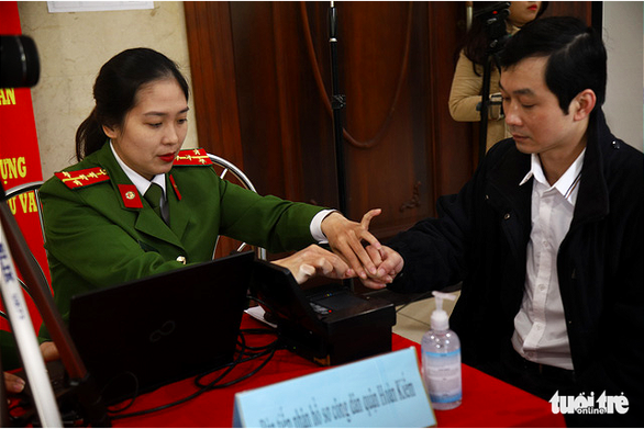 Hanoi police take fingerprint of a resident for the issuance of chip-based ID cards, December 31, 2020. Photo: Danh Trong / Tuoi Tre