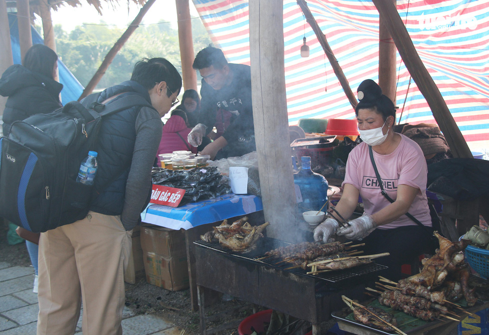 A visitor watch a woman grilling bushmeat skewers at a market fair showcasing products of the northern mountainous region held in the Culture-Tourism Village for Vietnamese Ethnic Groups in Son Tay District, Hanoi, January 1, 2021. Photo: H.Q. / Tuoi Tre