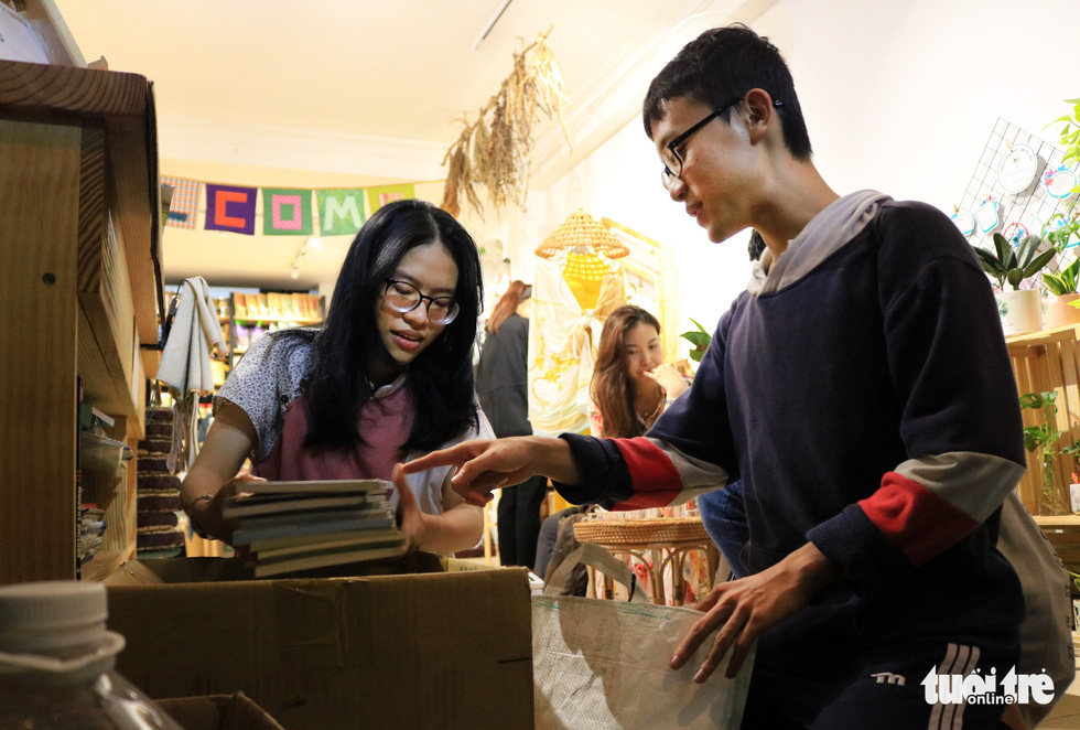 A visitor donates some old books at Tram Xanh. Photo: Nhat Thinh / Tuoi Tre