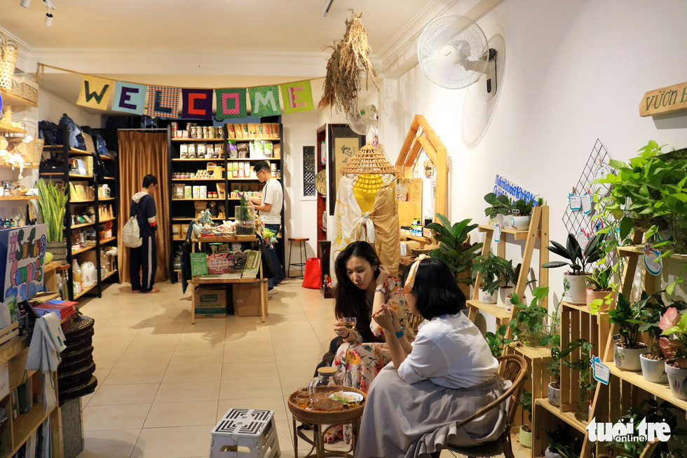 Two young women are drinking herbal tea at Tram Xanh while two other male visitors look at showcased items in a corner. Photo: Nhat Thinh / Tuoi Tre