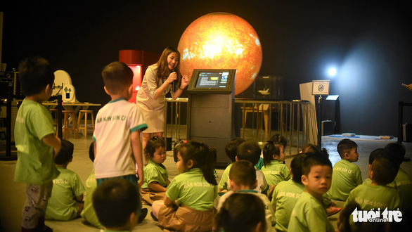 A staff from the Center for Scientific Discovery introduces a globe model containing planets in the solar system to a group children - Photo: Dung Nhan / Tuoi Tre