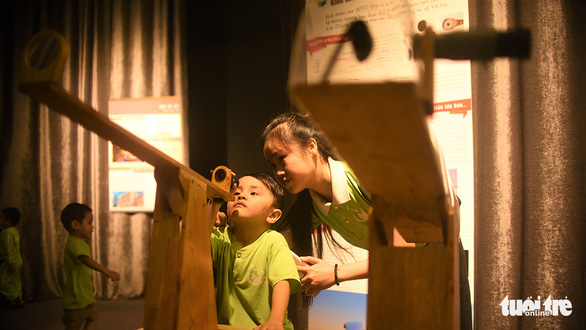 Two children look at a telescope in the Center for Scientific Discovery. Photo: Dung Nhan / Tuoi Tre