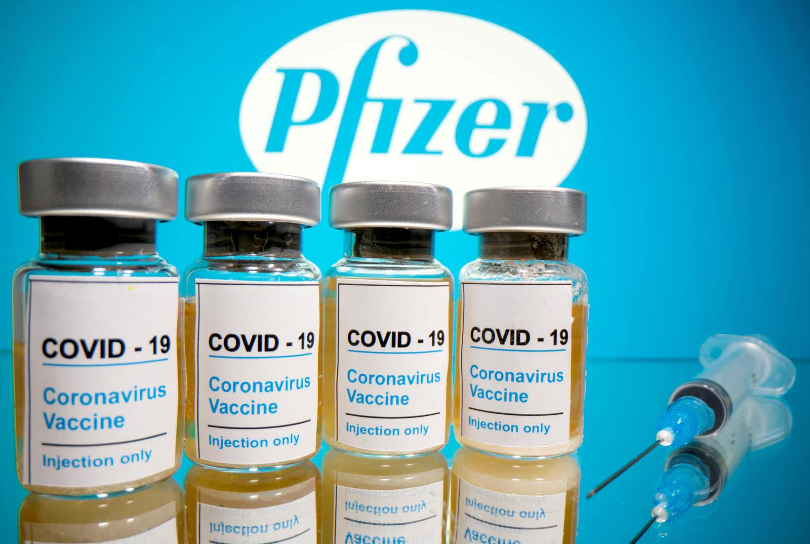 Vials with a sticker reading 'COVID-19 / Coronavirus vaccine / Injection only' and a medical syringe are seen in front of a displayed Pfizer logo in this illustration taken October 31, 2020. Photo: Reuters