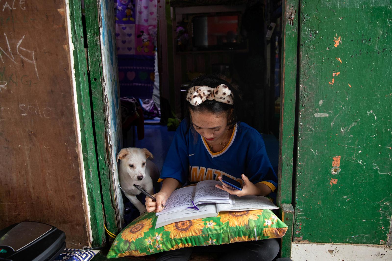 Annie Sabino, 16, a grade 9 student, completes her school work next to her dog, while tending to her family's sidewalk eatery beside their home, as schools remain closed during the coronavirus disease (COVID-19) outbreak, in Manila, Philippines, January 6, 2021. 'I often wake up late for class from staying up too late finishing online schoolwork, as the signal is better at night,' said Sabino. Photo: Reuters