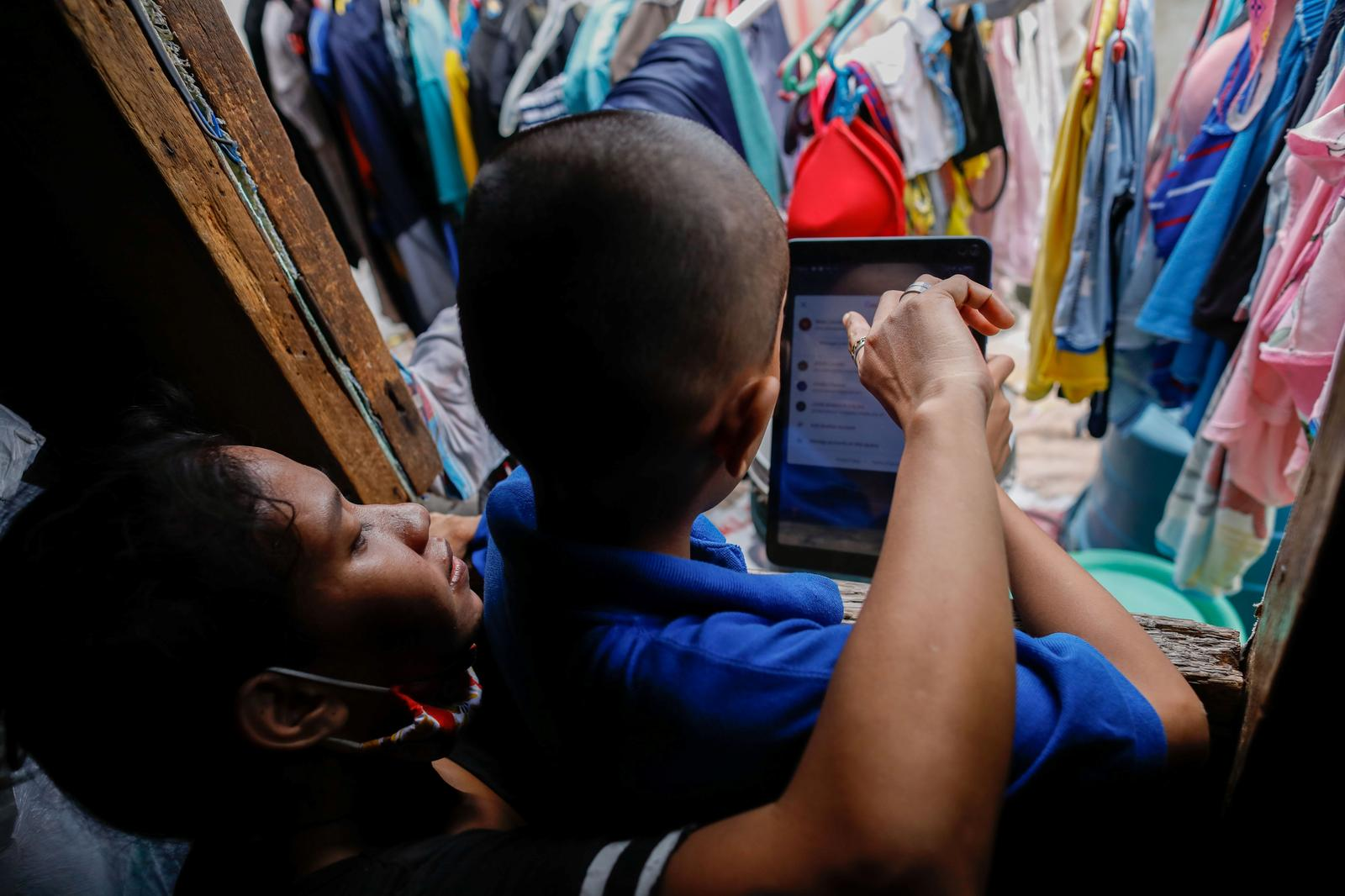 Jhay Ar Calma, 10, a grade 5 student, is helped by his mother Jonalyn Parulan as he prepares to take part in an online class with a tablet, provided to him by the local government, as schools remain closed during the coronavirus disease (COVID-19) outbreak, in their home in Sta. Mesa, Manila, Philippines, October 30, 2020. 'Sometimes we change the SIM card to a different provider so he doesn't have to study on the roof, but there's rarely enough money to spare for that,' Parulan told Reuters. Photo: Reuters