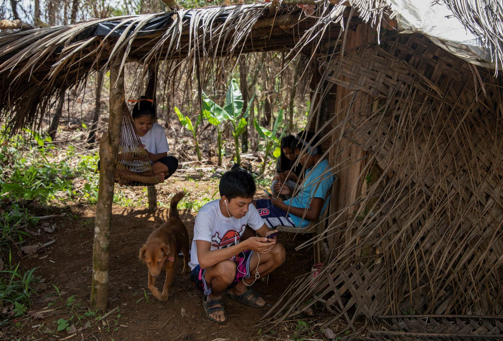 College students Jenebyl Cipres, 19, Almer Acuno, 21, Jester Rafon, 20, and Rosemine Gonzaga, 19, work on online worksheets in a hut on a mountain, as their community does not have enough signal for internet connection, following the suspension of physical classes during the coronavirus disease (COVID-19) outbreak, in Sitio Papatahan, Paete, Laguna, Philippines, October 22, 2020. 'I always fear I wouldn't be able to follow along to our lessons compared to my classmates who are in a better situation, in a more comfortable environment. I'm not jealous because I'm used to this way of living. I'm just scared to be left behind,' said Rafon. Photo: Reuters