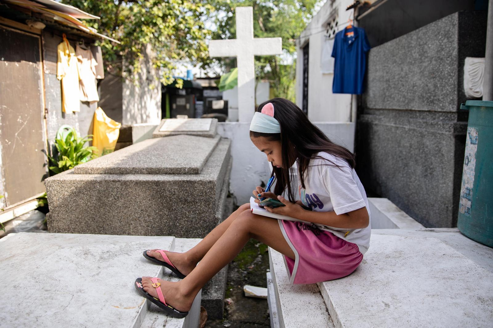 Grade 5 student Lovely Joy De Castro, 11, takes notes while attending an online class using a smartphone, as schools remain closed during the Coronavirus disease (COVID-19) outbreak, at Manila South Cemetery where she lives with her family in Makati City, Philippines, November 6, 2020. 'I just hope that she finishes school, gets a good job, and ultimately finds a life outside this cemetery,' said Castro's grandmother Angeline Delos Santos about her granddaughter. Photo: Reuters