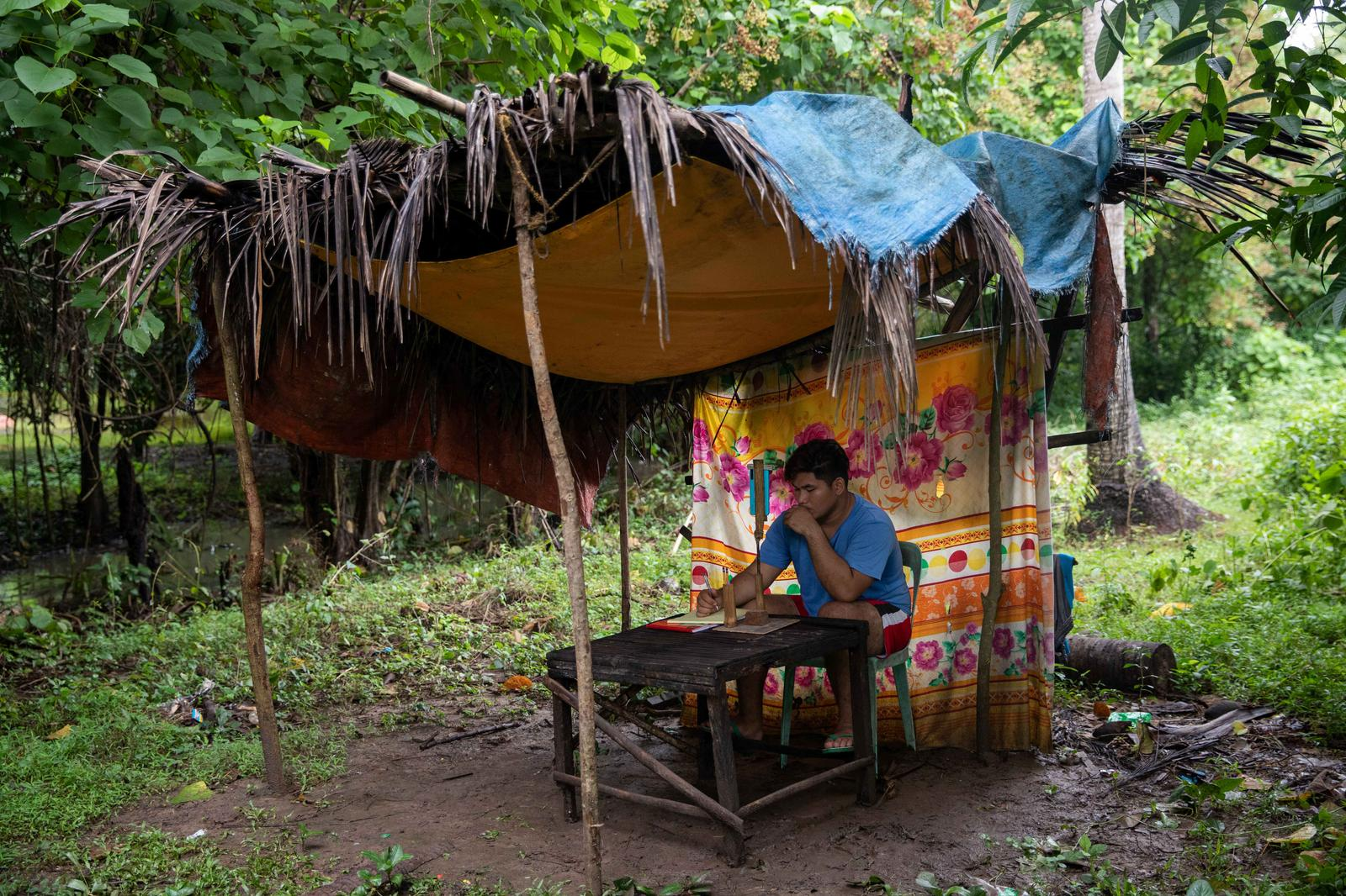 Mark Joseph Andal, 18, a college student, takes part in an online class through a smartphone at a forest hut where there is internet connection, following the suspension of physical classes during the coronavirus disease (COVID-19) outbreak, in Mabalanoy, San Juan, Batangas, Philippines October 15, 2020. Andal has taken a part-time job in construction to purchase a smartphone for virtual classes and has also built a forest shelter to capture an internet signal. When the signal fades, Andal picks up his plastic chair to move to another spot, and if it rains, he holds the phone in one hand and an umbrella in the other. 'We're not rich, and finishing school is my only way to repay my parents for raising me.' Photo: Reuters