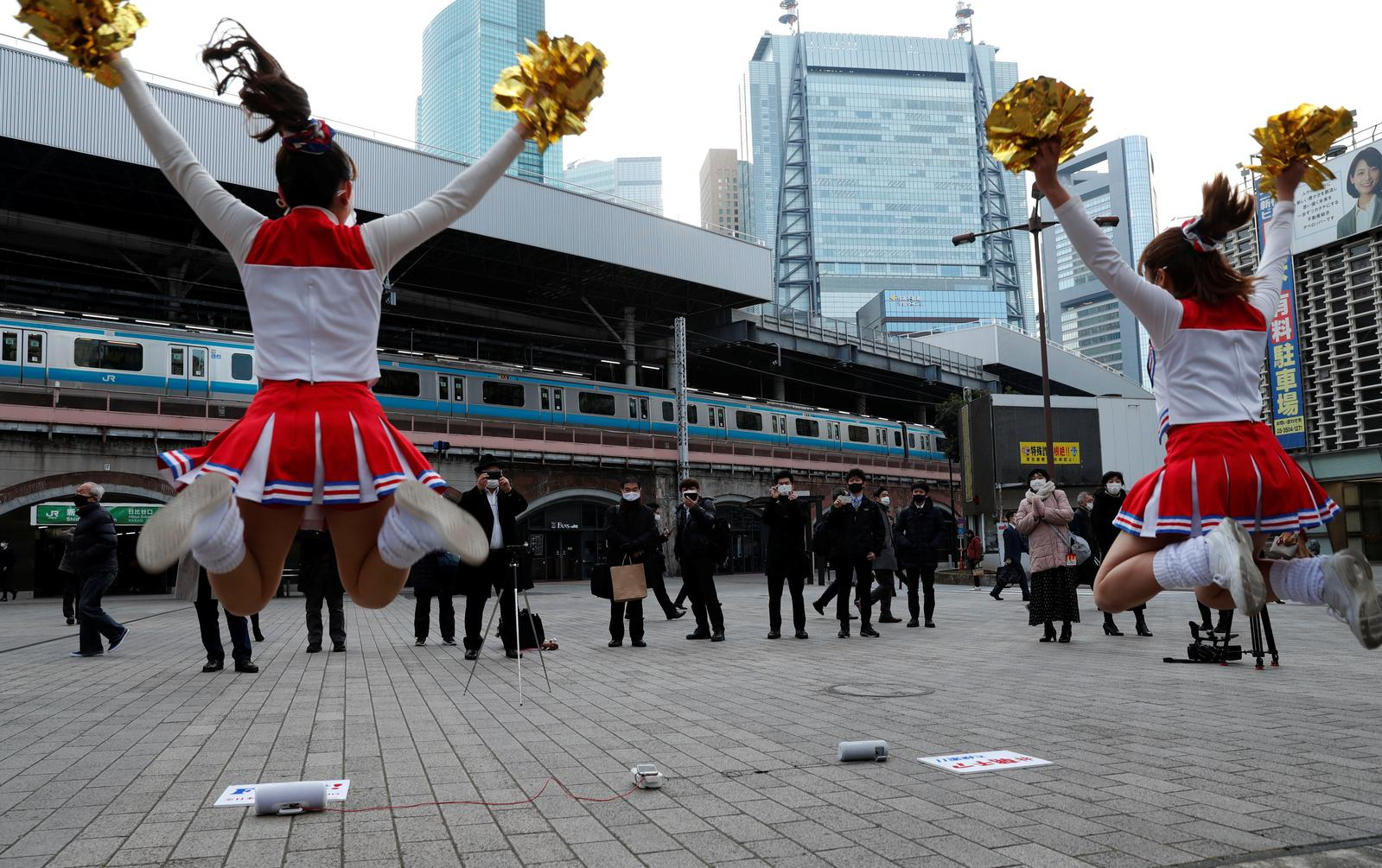 Cheerleaders wearing protective face shields, amid the coronavirus disease (COVID-19) outbreak, dance to cheer people up in front of Shimbashi Station during the commuting hour in Tokyo, Japan, January 7, 2021. Photo: Reuters