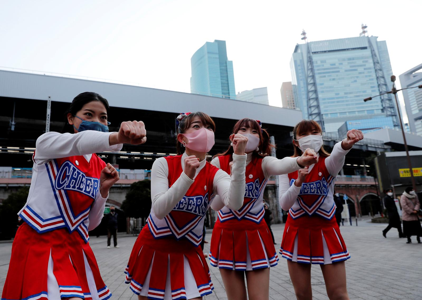 Cheerleaders wearing protective face shields, amid the coronavirus disease (COVID-19) outbreak, cheer people up in front of Shimbashi Station during the commuting hour in Tokyo, Japan, January 7, 2021. Photo: Reuters