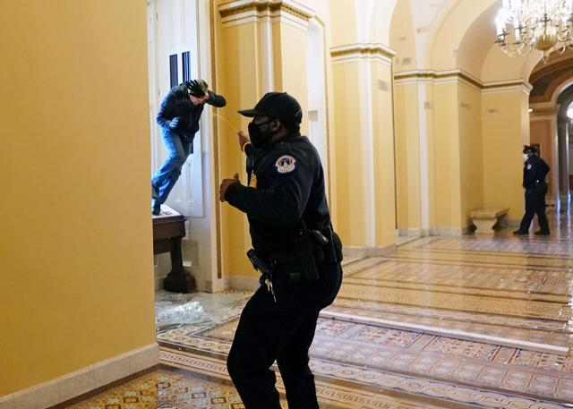 A U.S. Capitol police officer shoots pepper spray at a protestor attempting to enter the Capitol building during a joint session of Congress to certify the 2020 election results on Capitol Hill in Washington, U.S., January 6, 2021. Photo: Kevin Dietsch/Pool via Reuters
