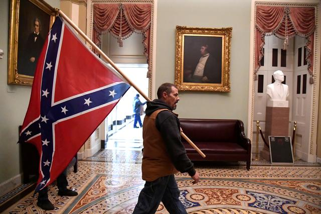 A supporter of President Donald Trump carries a Conferderate battle on the second floor of the U.S. Capitol near the entrance to the Senate after breaching security defenses, in Washington, U.S., January 6, 2021. Photo: Reuters