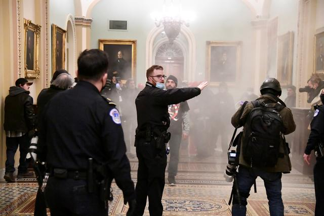 A security officer gestures after supporters of U.S. President Donald Trump breached security defenses at the U.S. Capitol, in Washington, U.S., January 6, 2021. Photo: Reuters