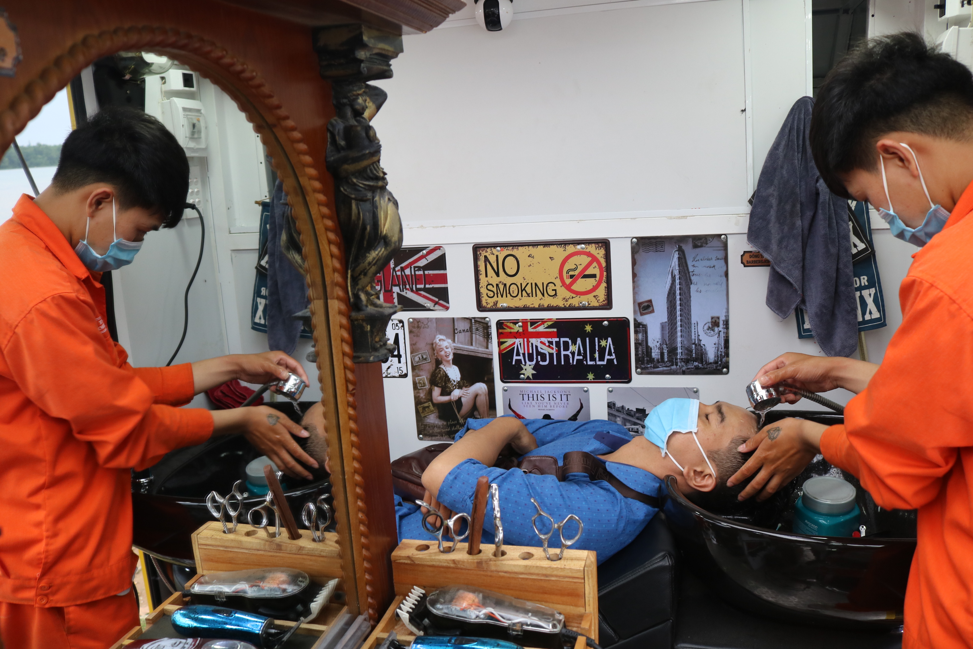 A barber washes a customer hair at Dong Tay mobile barbershop, District 2, Ho Chi Minh City. Photo: Hoang An / Tuoi Tre