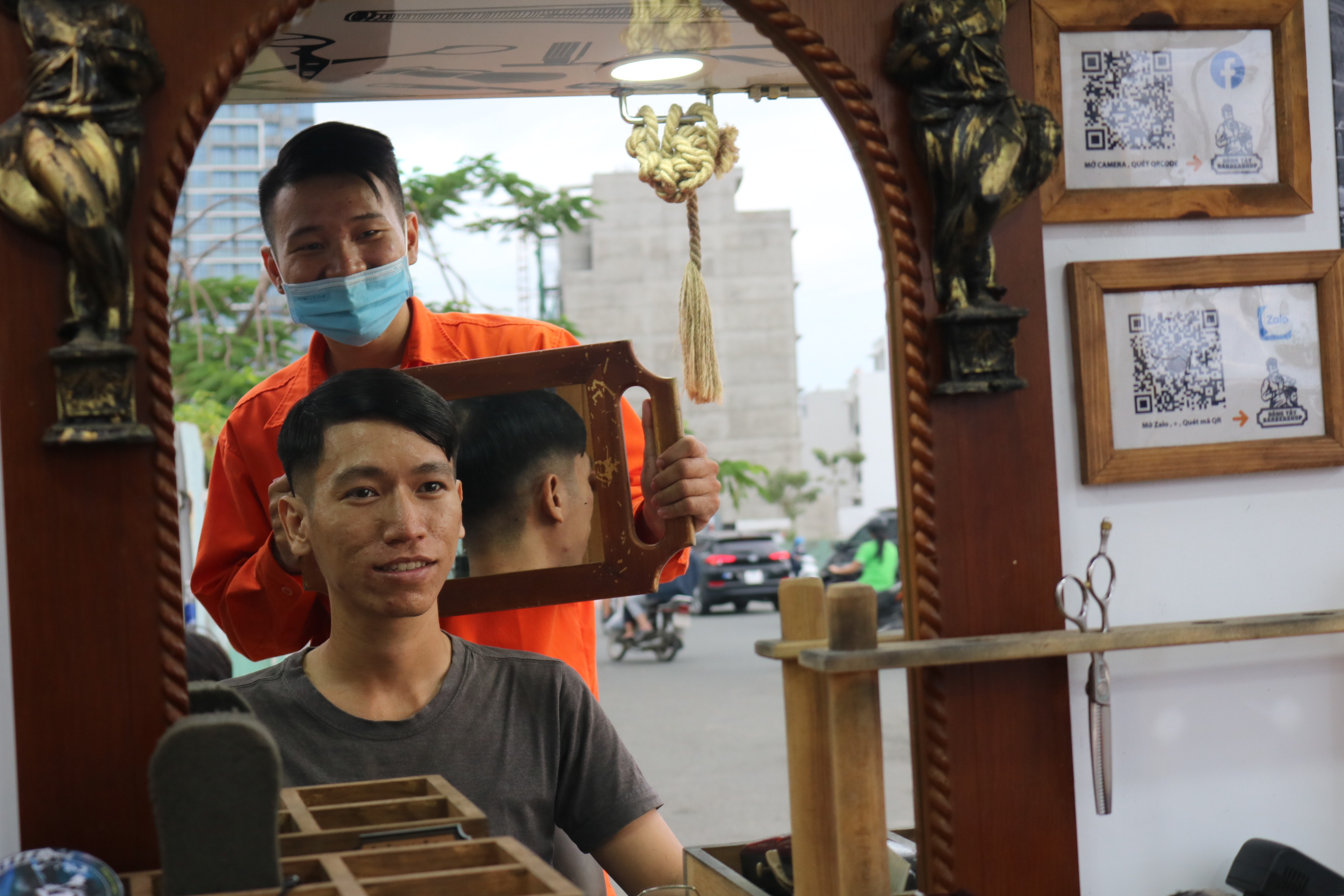 A barber shows a customer his new hairstyle after having a haircut at Dong Tay mobile barbershop, District 2, Ho Chi Minh City. Photo: Hoang An / Tuoi Tre