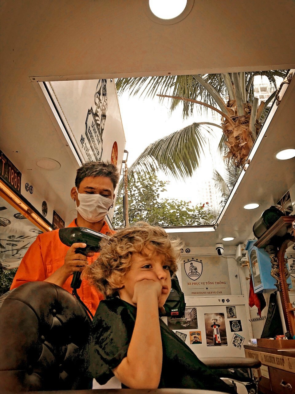 In this supplied photo, aforeign kid enjoys the haircut service at Dong Tay mobile barbershop, District 2, Ho Chi Minh City.