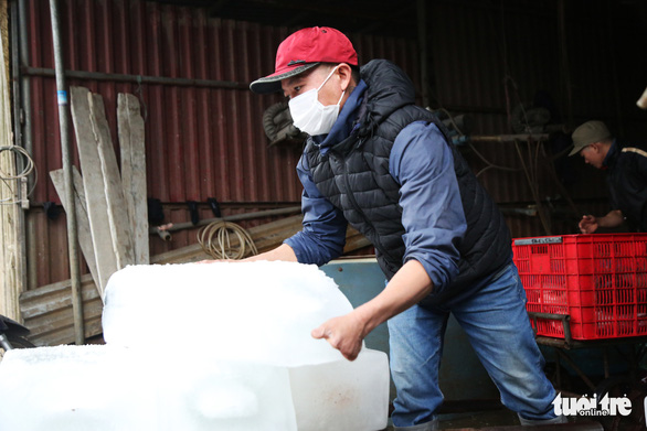 An ice carrier moves a big block of ice with his bare hands in shivery Hanoi, Vietnam. Photo: Ha Quan / Tuoi Tre