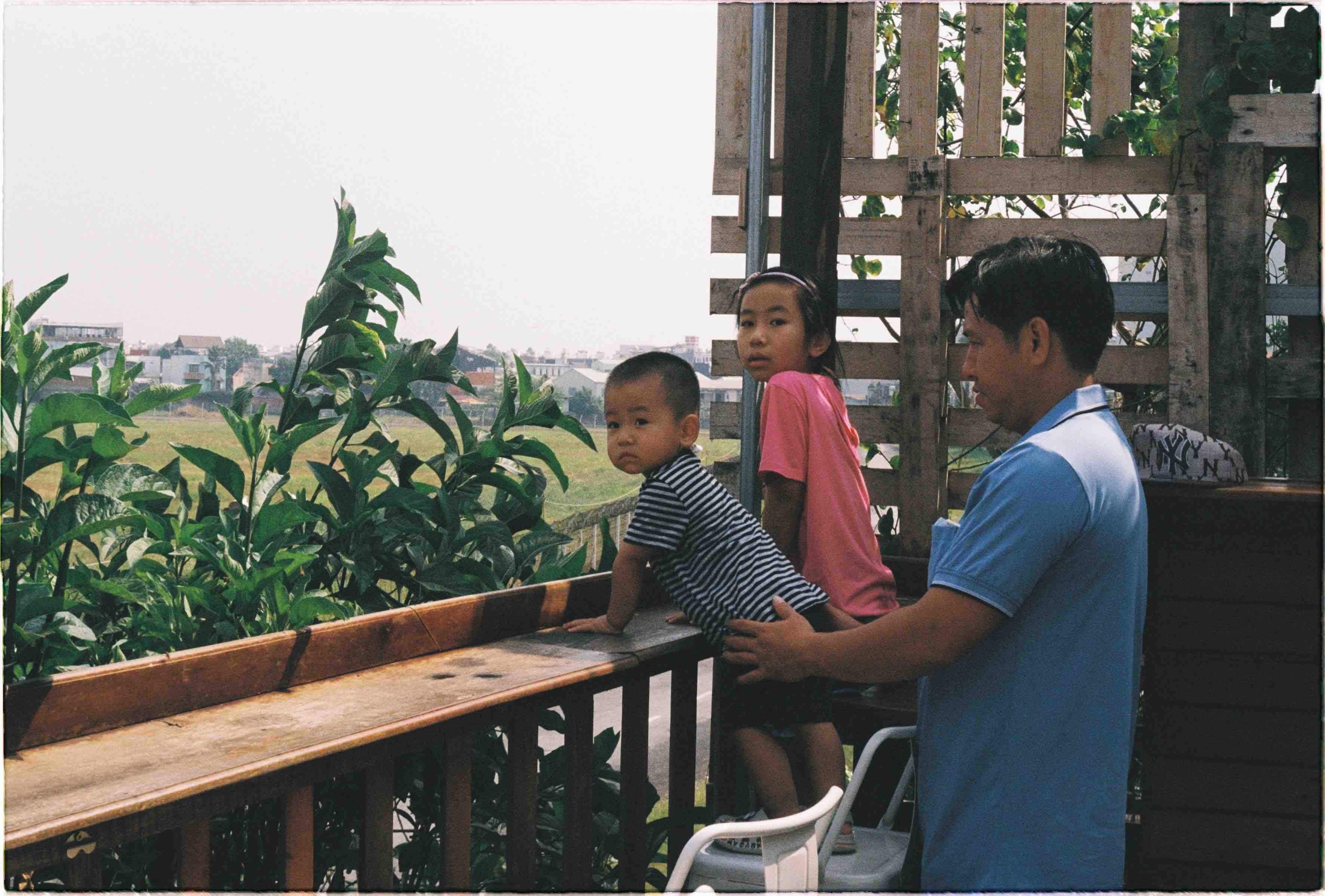 A man holds his children as they watch a plane fly by at Phen's café in in Go Vap District, Ho Chi Minh City. Photo: Linh To / Tuoi Tre