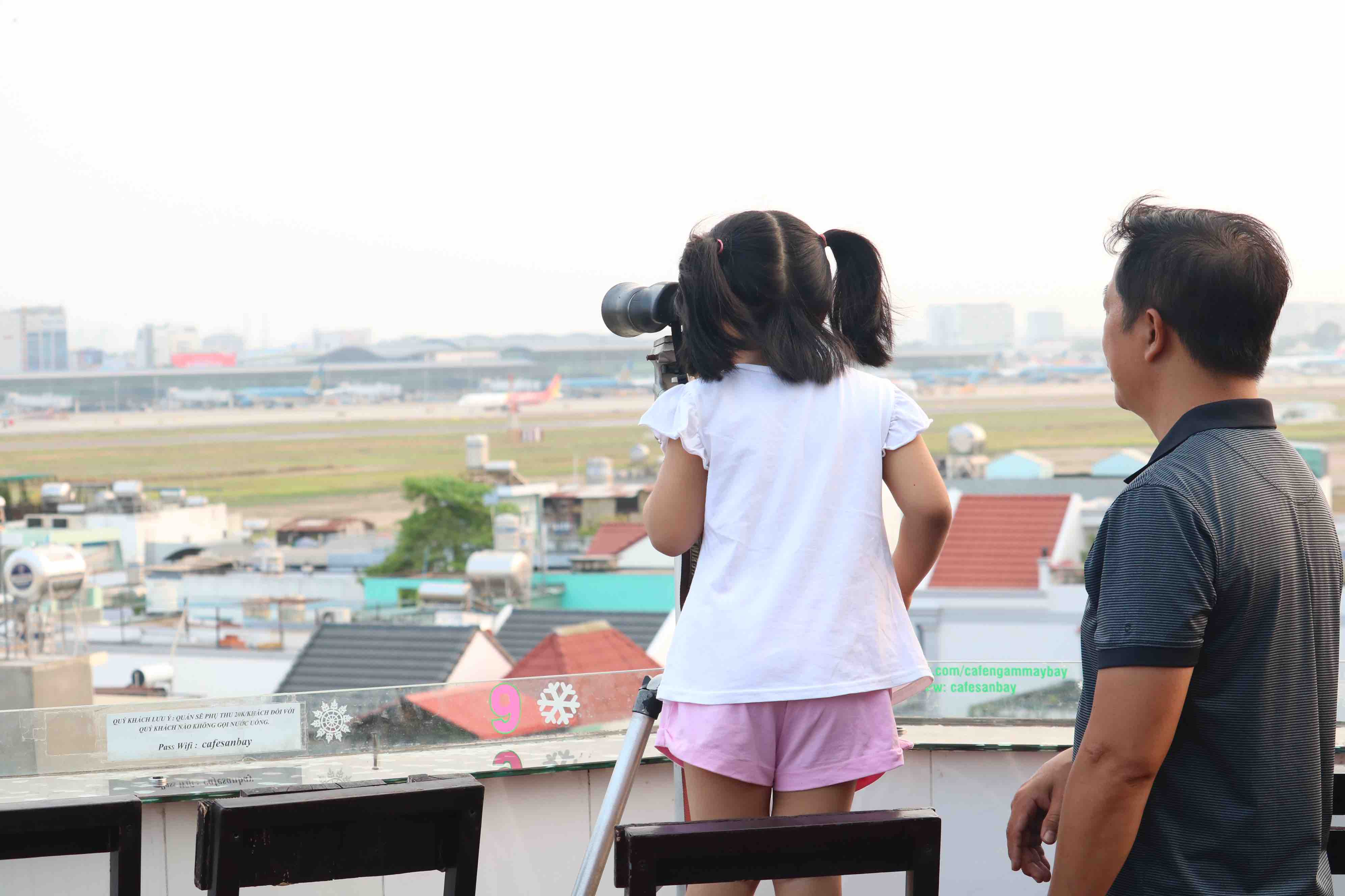 Luu Ngoc Tuan, the owner of Ngam May Bay, teaches his daughter how to use binoculars to watch planes in Go Vap District, Ho Chi Minh City. Photo: Hoang An / Tuoi Tre
