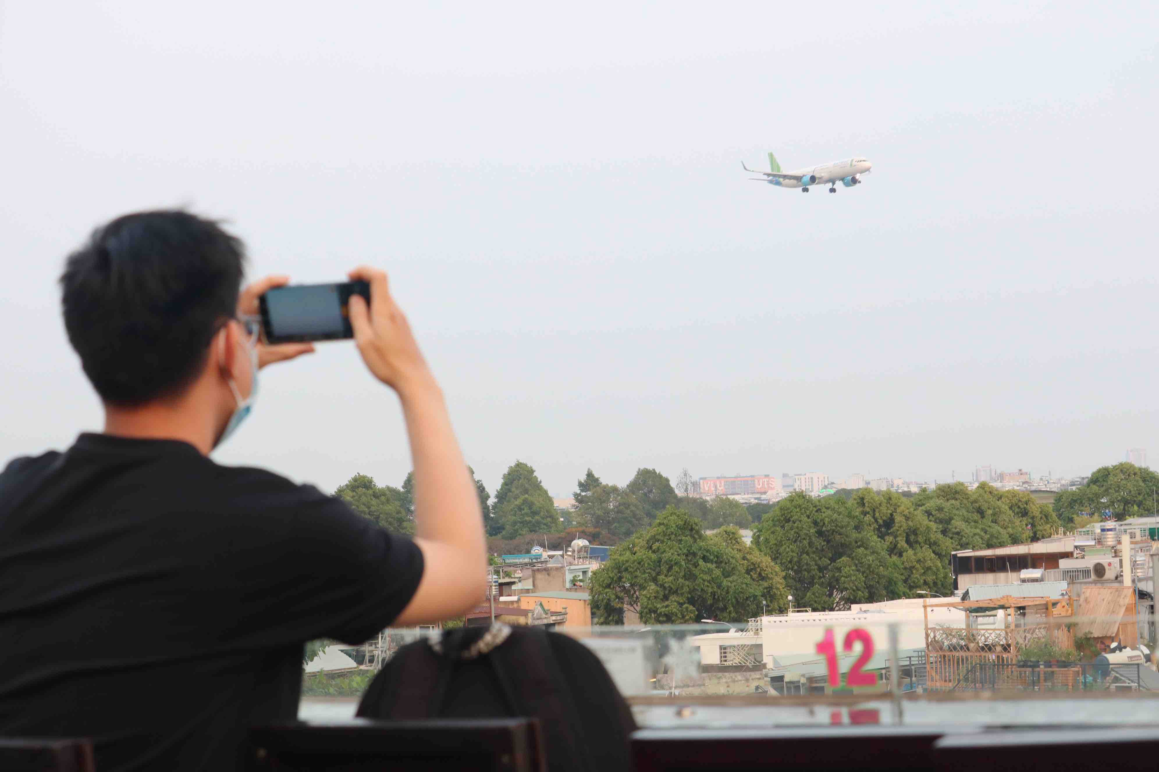 A customer photographs an airplane as it passes by at Ngam May Bay café in Go Vap District, Ho Chi Minh City. Photo: Hoang An / Tuoi Tre
