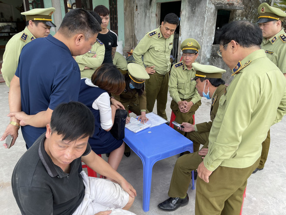 Market surveillance officials write an administrative record on the violations at a warehouse that stores fake designer bags in Nam DInh Province, in this supplied photo taken March 17, 2021.