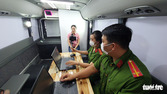 A resident takes profile photo for her chip-based ID card in a travelling service booth in Ho Chi Minh City, March 18, 2021. Photo: Minh Hoa / Tuoi Tre