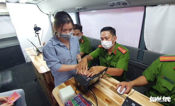A resident submits fingerprints for her chip-based ID card in a travelling service booth in Ho Chi Minh City, March 18, 2021. Photo: Minh Hoa / Tuoi Tre