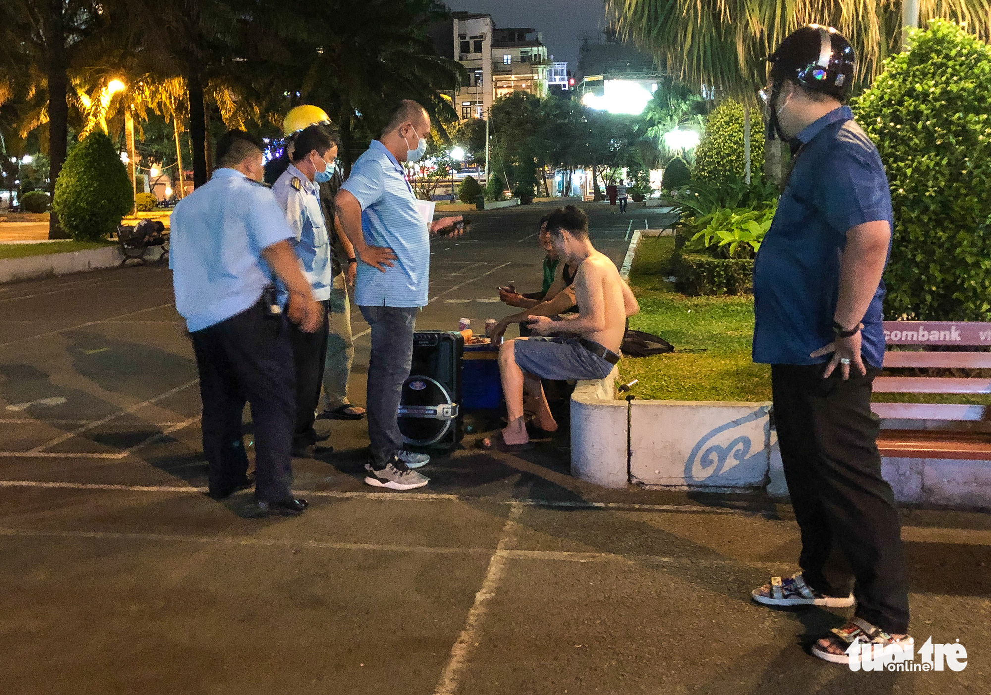 Officials remind a group to turn off their portable loudspeader, which they used for singing, at the September 23 Park in Ho Chi Minh City, Vietnam, March 20, 2021. Photo: Chau Tuan / Tuoi Tre