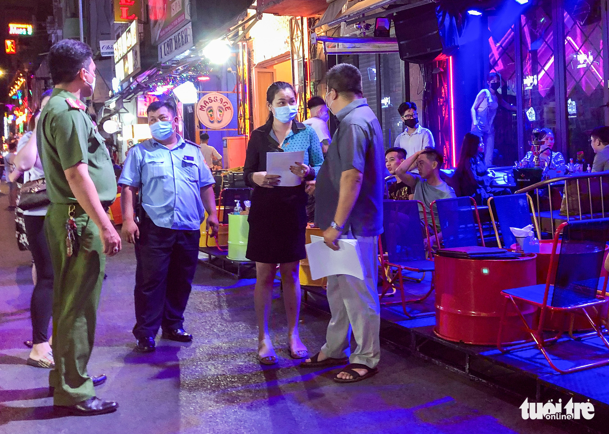An official explains to a store owner the terms of a noise-reducing commitment during an inspection of businesses on Bui Vien Street in Ho Chi Minh City, Vietnam, March 20, 2021. Photo: Chau Tuan / Tuoi Tre