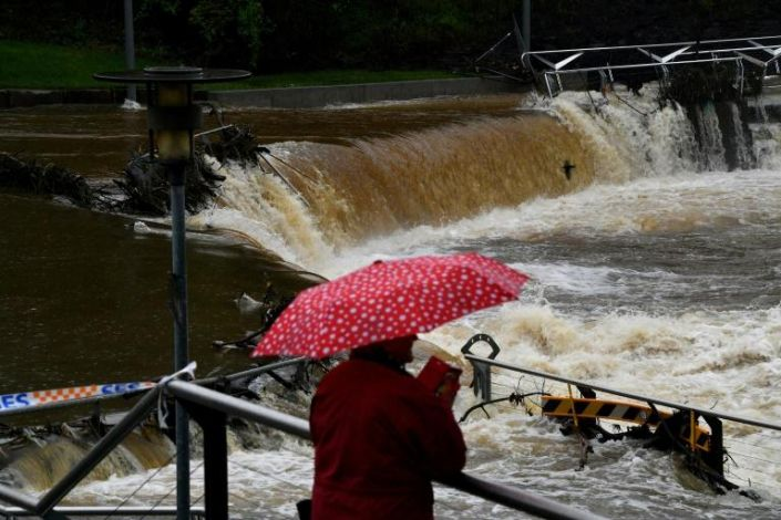 A woman takes pictures of the overflowing Parramatta river in Sydney on March 22, 2021 as Sydney braced for its worst flooding in decades after record rainfall caused its largest dam to overflow and as deluges prompted mandatory mass evacuation orders along Australia's east coast. Photo: AFP