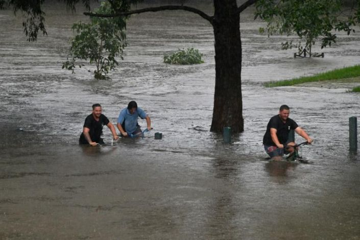 People ride their bicycles through a flooded park on the banks of Nepean river in Penrith suburb on March 21, 2021, as Sydney braced for its worst flooding in decades after record rainfall caused its largest dam to overflow and as deluges prompted mandatory mass evacuation orders along Australia's east coast. Photo: AFP
