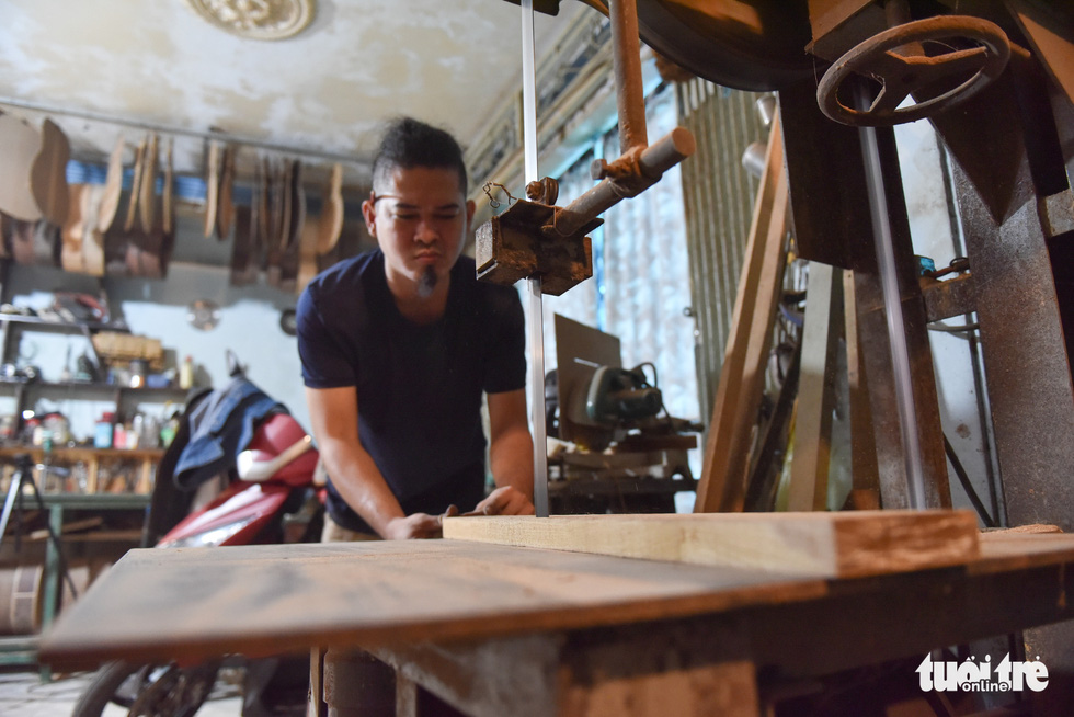 Thang handles a piece of wood in his workshop. Photo: Ngoc Phuong/Tuoi Tre.